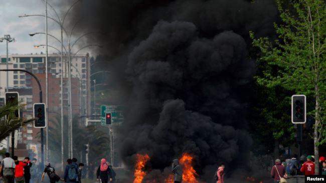 Manifestantes enmascarados junto a una barricada incendiada en Santiago de Chile el 20 de octubre de 2019 / REUTERS