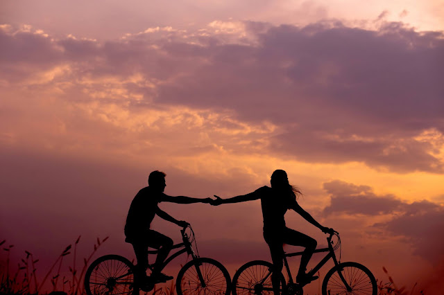 A couple on a bike holding hands silhouetted against a sunset