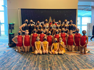girls from Arena Dance Academy in matching dance costumes and masks are lined up and smiling