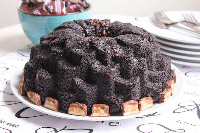 Food Lust People Love: This Snickers Bundt Cake is rich and super chocolate-y with a tender crumb. The Snickers pieces sink to the bottom of the pan while baking which means the top of the cake is full of them! Pour yourself a cold glass of milk and enjoy a large slice!