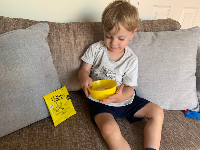 Toddler eating Liobites banana crisp snacks