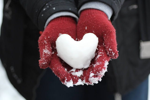 Person wearing red mittens holding a snowball shaped like a heart