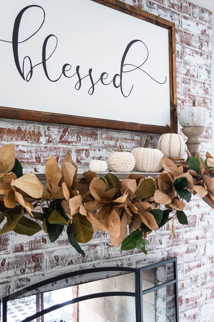 white painted brick fireplace, neutral pumpkins and brown leaf garland