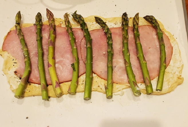 this is phyllo dough with hot capicola ham on it and asparagus spears that will be rolled in twists for any appetizer