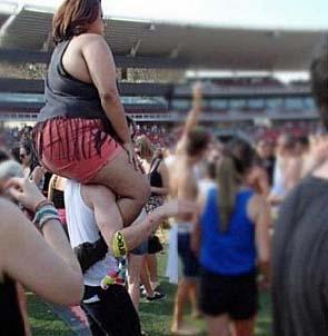 Lustige dicke Frau auf Männer-Schultern tragen zum lachen