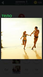 молодые люди летом на пляже бегают под солнцем