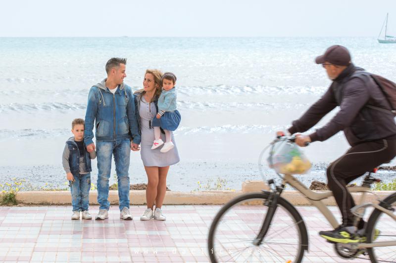padres con hijos playa y ciclista