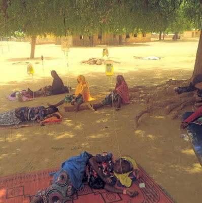 PHOTO: Sick Nigerian Women Receiving Drip Under A Tree