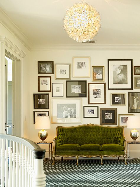 Dramatic art gallery wall over green velvet vintage sofa Ken Fulk