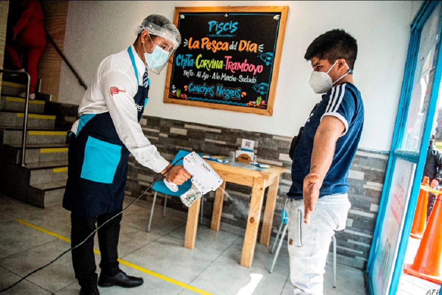 Un peruano es desinfectado al llegar a un restaurante en Lima. Pero esas medidas de prevención no las toman en las reuniones familiares, por lo que quedan prohibidos los quinceaños, las fiestas de primera comunión, y otras celebraciones familiares / AFP