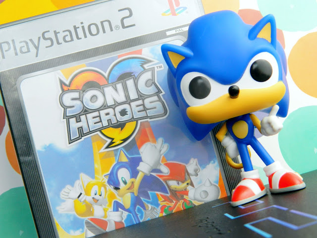 A photo showing a playstation 2 consule, a game called Sonic Heroes, a figure of Sonic who is a blue hedgehog character by Sega and a dotty background