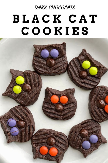 White plate filled with dark chocolate black cat cookies.