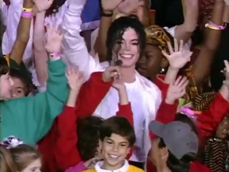 子供たちに囲まれて笑顔で右手を振るマイケル・ジャクソン