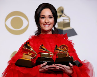 Country singer Kacey Musgraves, holding the four Grammys she won in 2019.