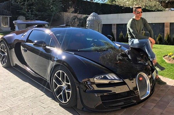 Cristiano Ronaldo sitting on top of the fast and expensive Bugatti Veyron