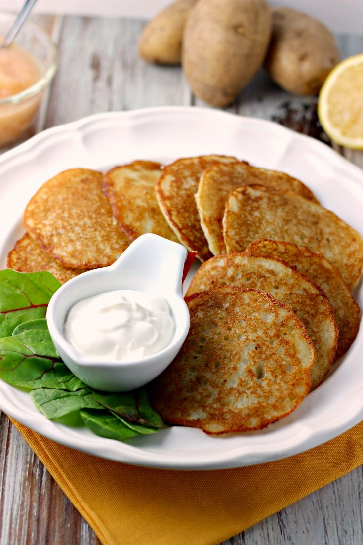 Easy Potato Pancakes by Renee's Kitchen Adventures on a white plate with a lettuce garnish and sour cream. Applesauce and potatoes in the upper top background.