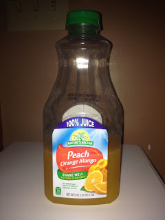 An empty bottle of Nature's Nectar Peach Orange Mango 100% Juice, from Aldi