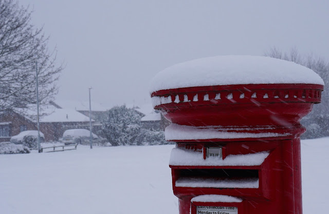 Red postbox in snow