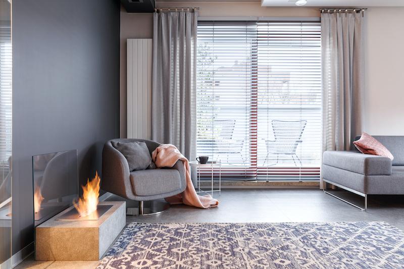 Tendencias decoración interiores 2021, sala con chimenea y alfombra oriental.