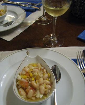 prato de petiscos com feijões e um copo de vinho branco