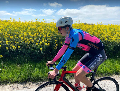 Oskar Revelj på sin tävlingscykel i belgiska lagets cerise-blå dress, med gult blomsterfält i bakgrunden.