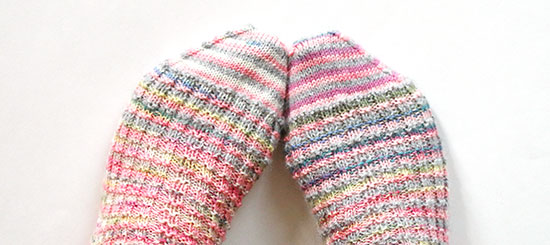 Top view of feet wearing hand knit striped pastel socks on a white background.