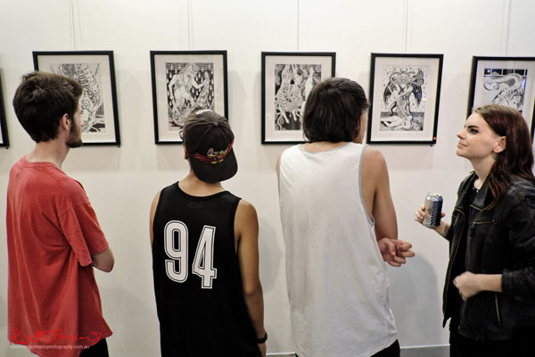 Three male friends looking at art, artist Sarah looks on. GORO at m2 gallery. Photographed by Kent Johnson for Street Fashion Sydney.