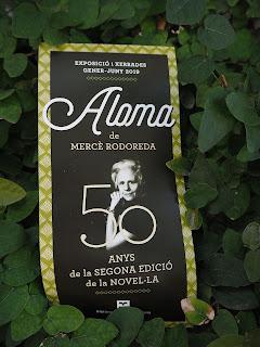 """Circular publicitària de l'Exposició itinerant """"Aloma de Mercè Rodoreda. 50 anys de la segona edició de la novel·la"""" fotografiada a l'heura arrapada a la caseta de jardiners, jardineres del Parc de les Aigües, tocant al Carrer de les Camèlies i a la Biblioteca Guinardó-Mercè Rodoreda (Barcelona) per Teresa Grau Ros"""