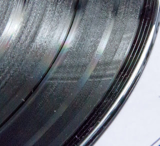 [Image: Close-up of a vinyl record showing a wavy pattern.]