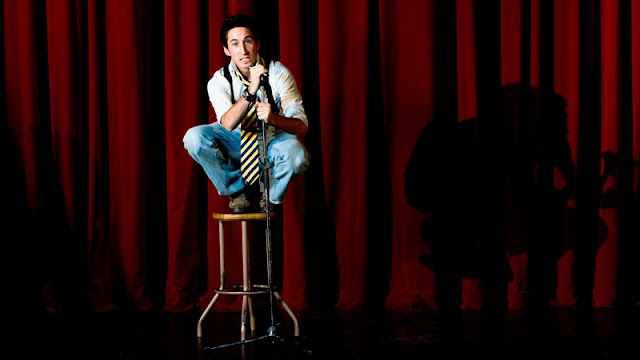 comedian sitting on stool
