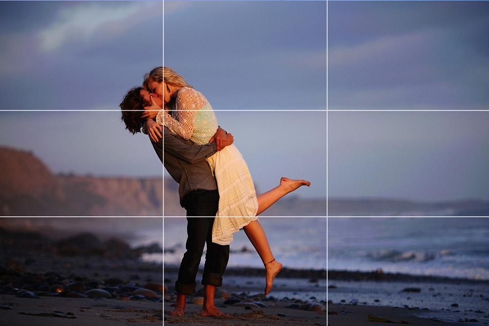 Komposisi foto prewedding pose ciuman dengan pasangan di pinggir pantai