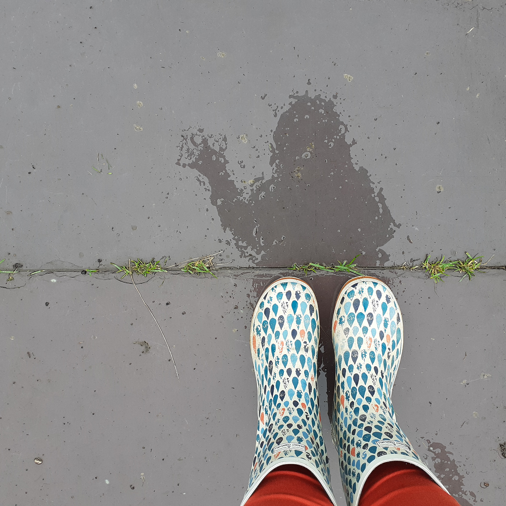 Reflection on wet path of a person waving