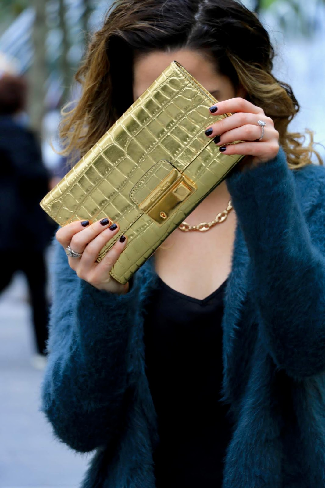 Nyc fashion blogger Kathleen Harper carrying a gold Michael Kors clutch.