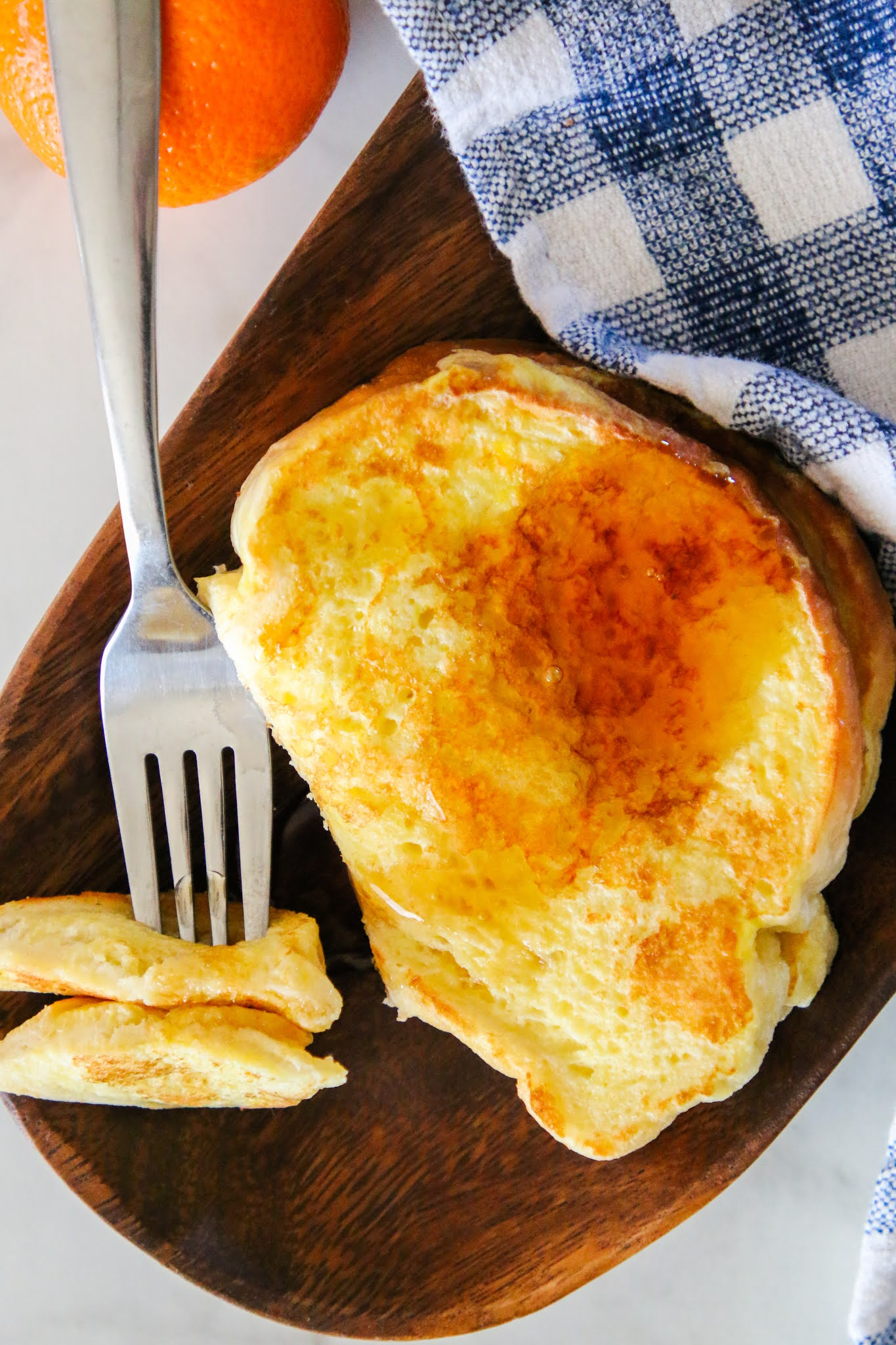 Two pieces of French Toast on a wood plate with a blue dish towel and an orange in the background. There is a for holding a bite of the French Toast.