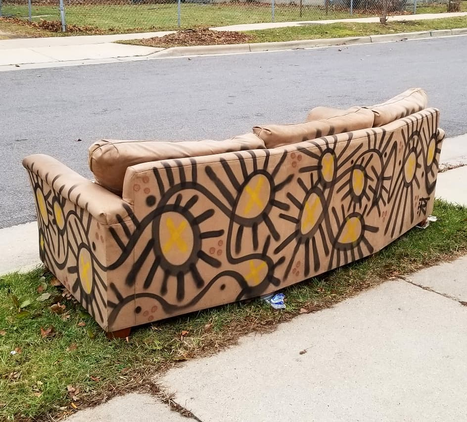 Image contains street art outdoors on couch