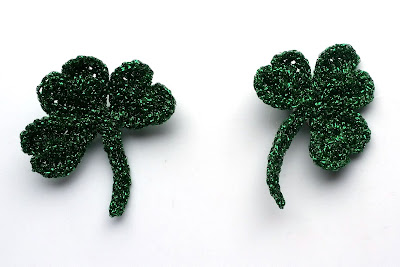 Two completed crocheted shamrocks made of green sparkly metallic yarn.  The shamrocks have three heart-shaped leaves, joined at their points and connected to a stem.