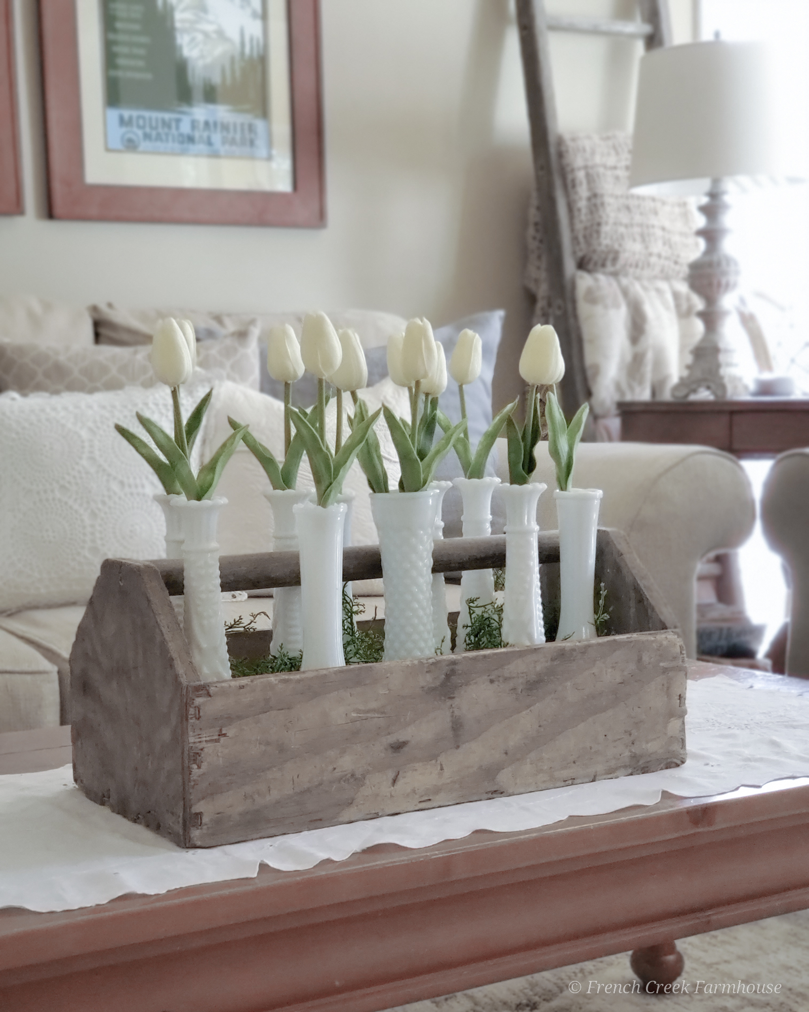 Wood toolbox filled with milk glass vases and white tulips