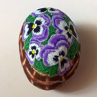 Pansies in a basket painted on a stone by Cindy Thomas