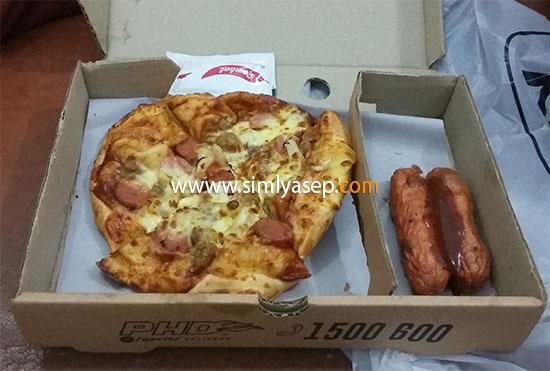 NIKMAT : Inilah paket MyLunch Box Pizza HUT yang terdiri dari 1 loyang pizza hut ukuran mediium, 2 buah sosis, dan 1 botol Cappunico Jelly, tidak tampak dalam foto.  Foto Asep Haryono