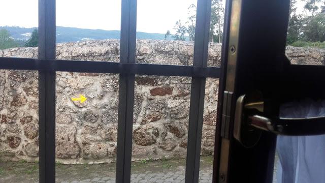 uma seta amarela num muro de pedras, vistos de uma  janela
