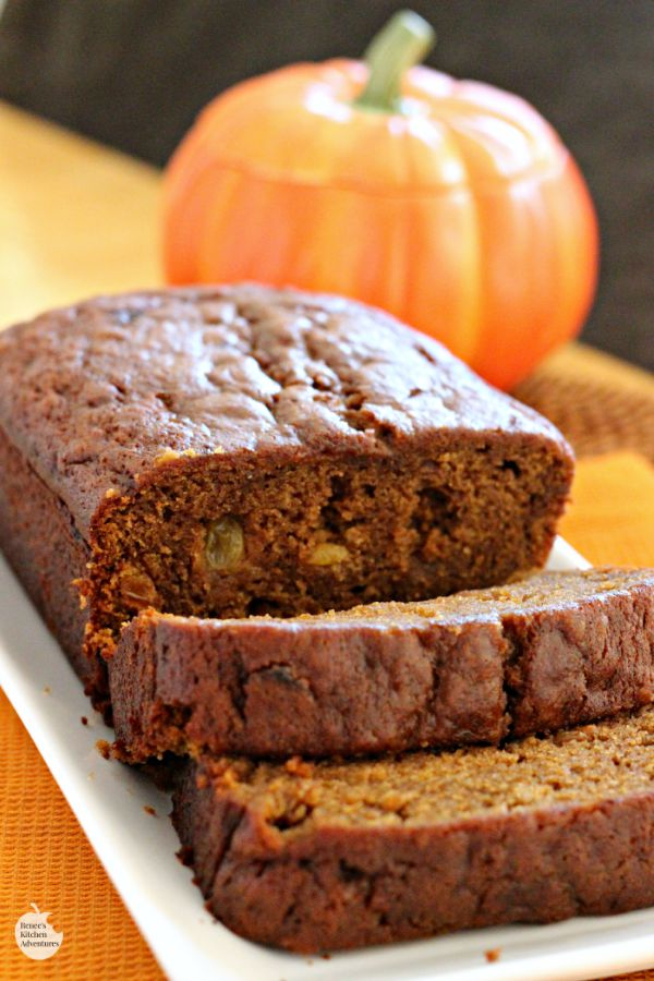 Spiced Pumpkin Bread by Renee's Kitchen Adventures on a white tray sliced with a pumpkin in the background
