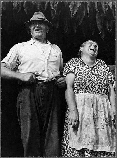 Beautiful black and white photo of an old couple laughing outside in the yard