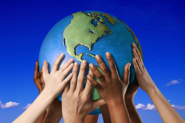 hands holding a globe of the earth in a blue sky