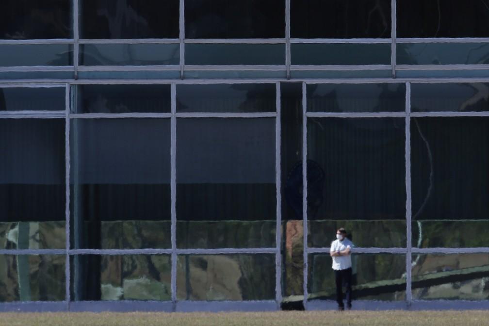 """Jair Bolsonaro es visto en aislamiento frente al """"Palácio da Alvorada"""" (Residencia Oficial), en Brasilia. El presidente confirmó esta semana que dio positivo en prueba de COVID19"""