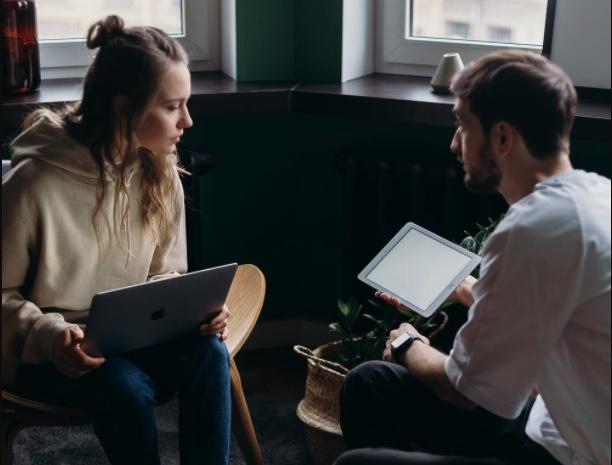 Mujer y hombre sentados uno frente al otro con un dispositivo electrónico portátil cada uno