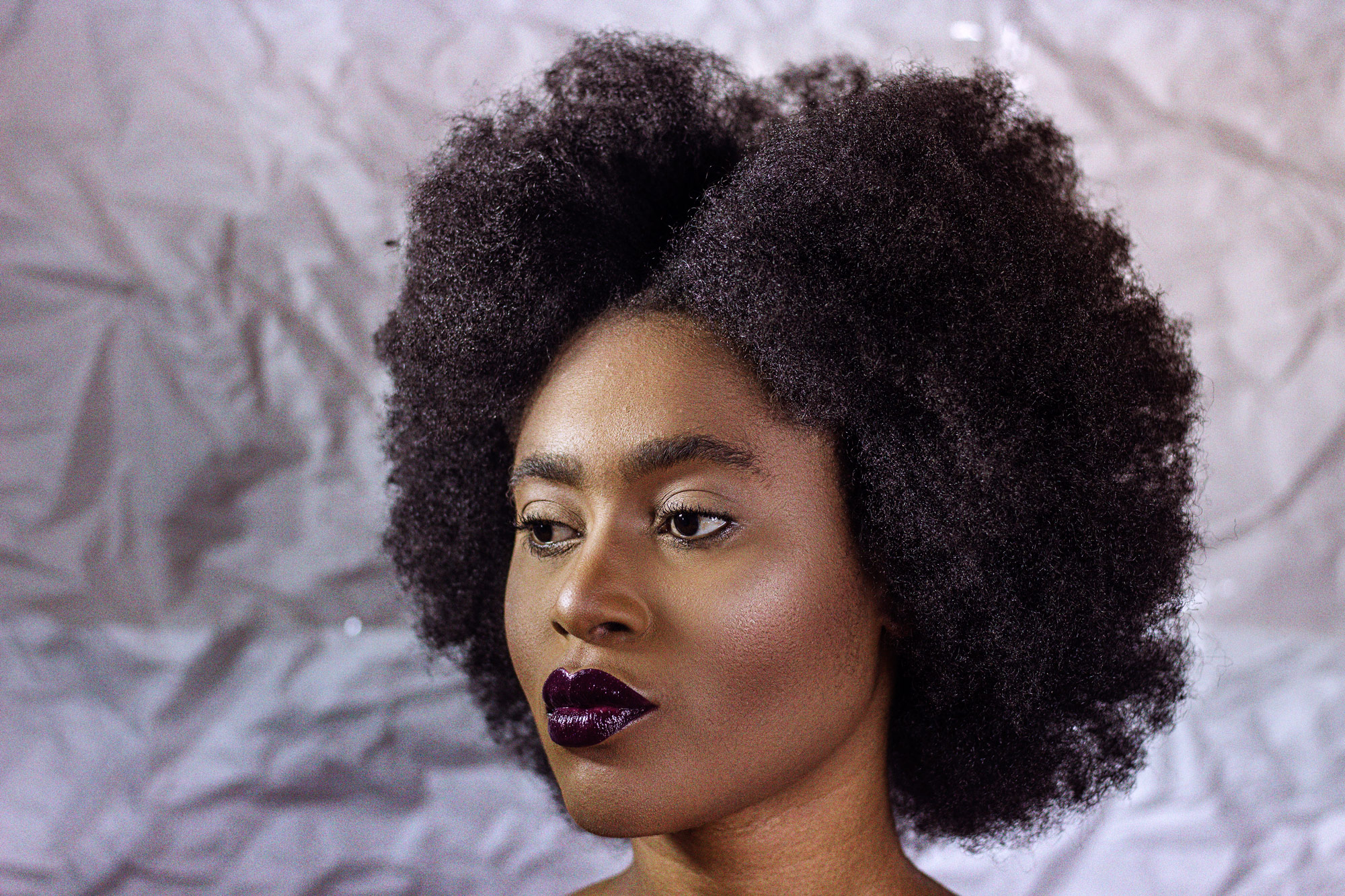 Beauty editorial smiling African woman with afro purple glossy lips