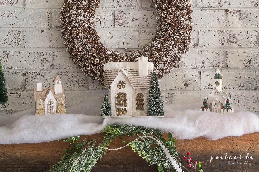Christmas mantel with pine cone wreath, snowy little houses, cedar garland
