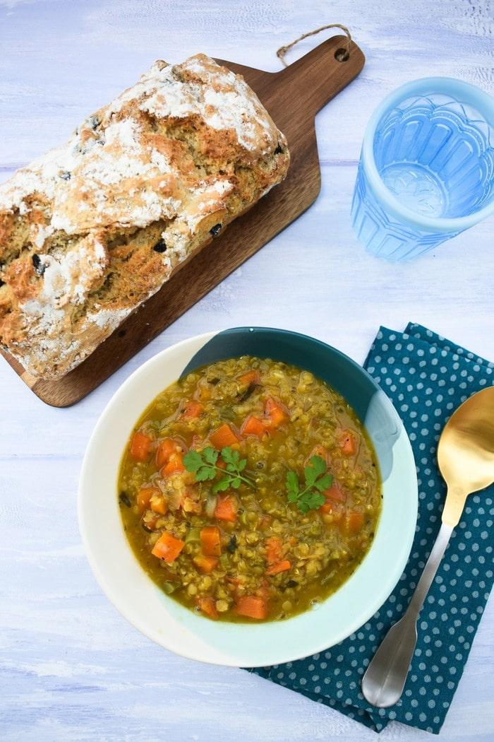Bowl of Broccoli, Carrot & Lentil Soup alongside loaf of black olive beer bread