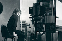 A black and white photograph of a smiling woman in a room filled with camera equipment and a bookshelf.