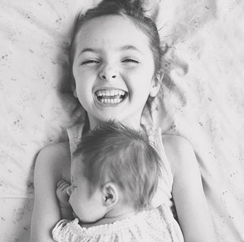 little girl laughing with baby